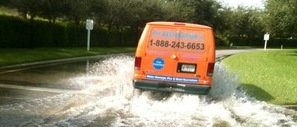 Water and Mold Damage Restoration Van Driving Down Flooded Street